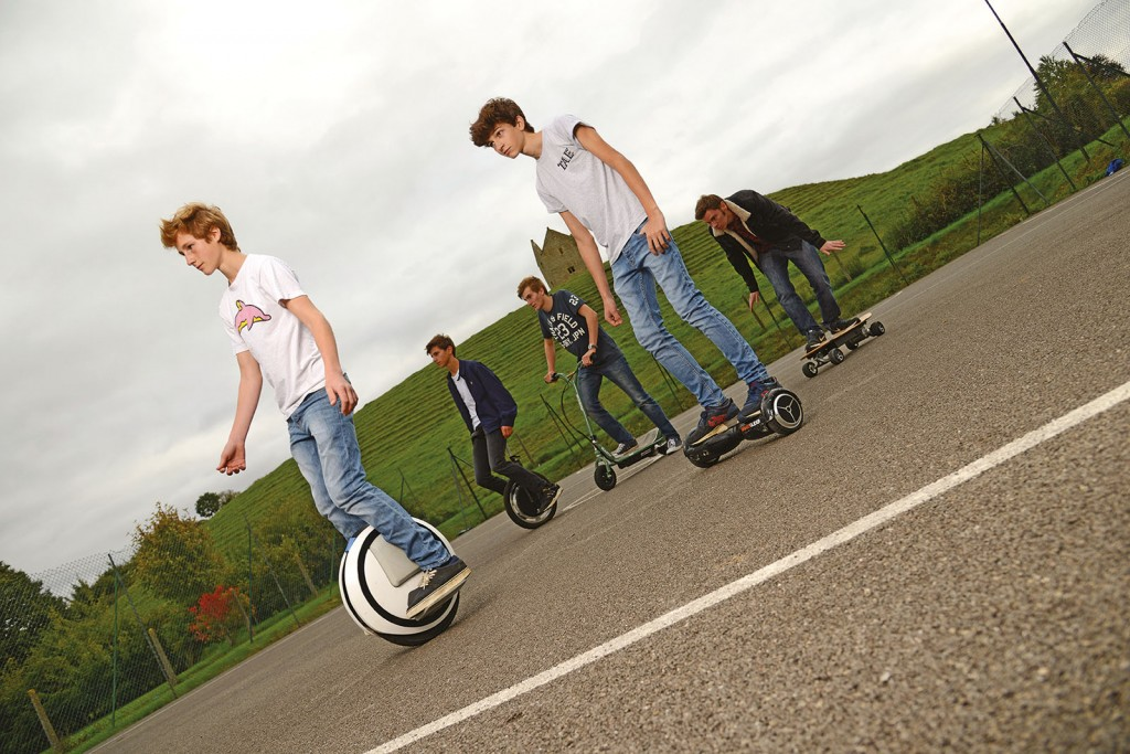 Location shot of teenagers riding a variety of rideables in a park. You'll notice Jack looking very natural at the back.