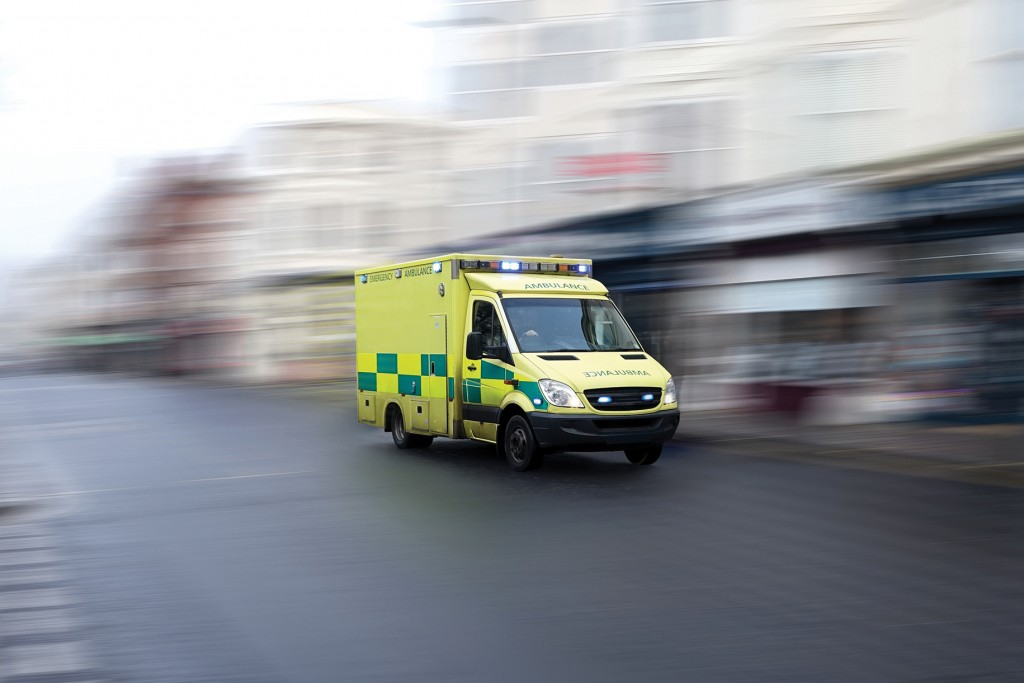 Picture of a yellow emergency ambulance rushing through a city to the hospital with full flashing blue lights and siren. Speed is emphasized by the motion blurred urban background. Vehicle is generic: no visible making or brand. License plate and other markings are also removed.