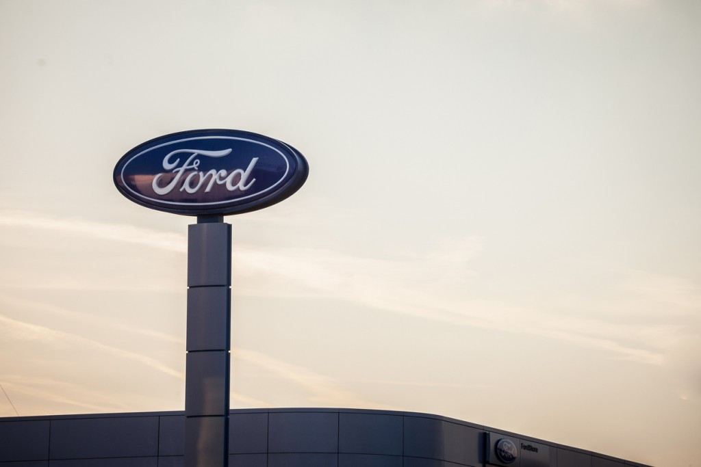 Picture of the Ford sign with their logo on their car dealership in New Belgrade, taken at sunset. Ford Motor Company is an American multinational automaker selling automobiles and commercial vehicles