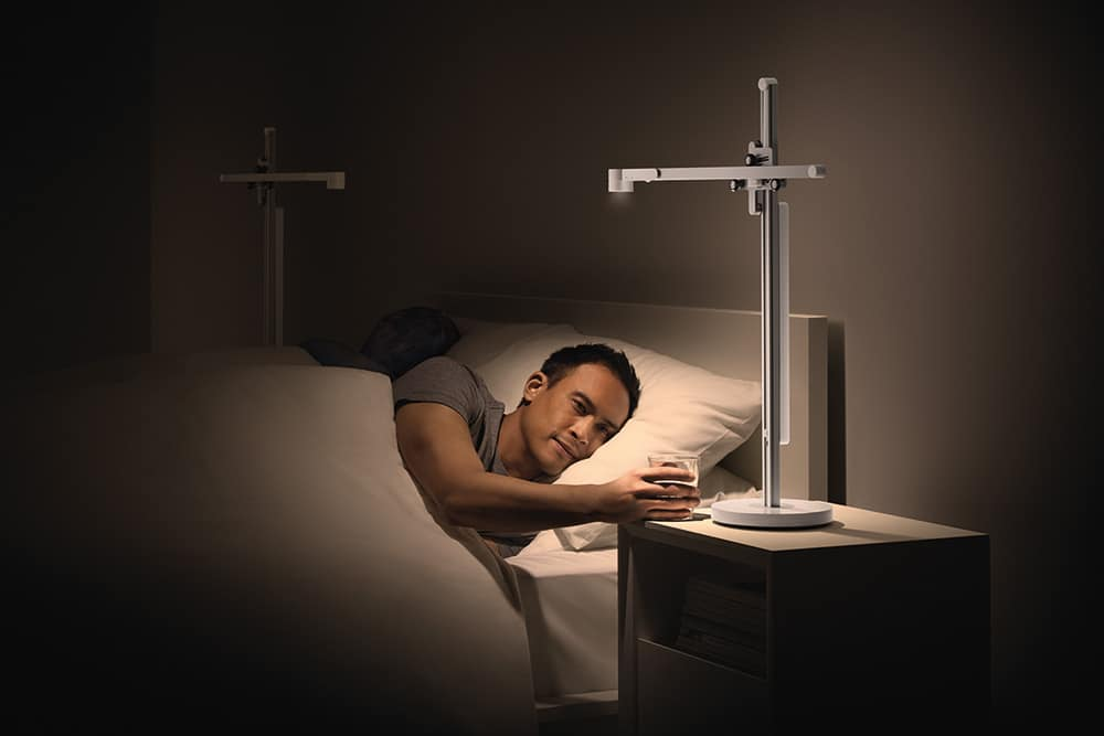 Lightcycle being used by a couple in bed, man reaching for glass of water, light is personal/targeted  on him, warm low lux light, 2700K