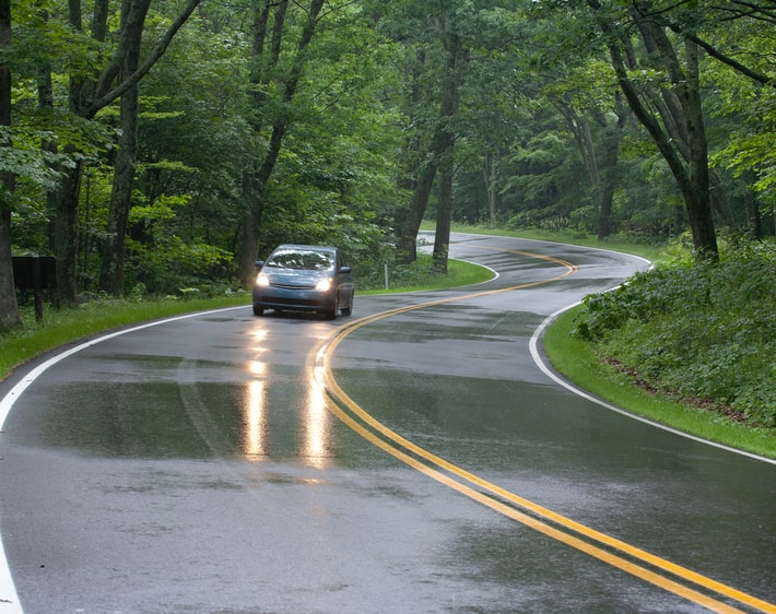 hatchback-driving-down-winding-wet-road