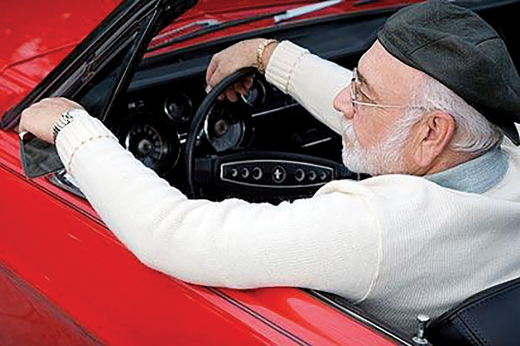 A7TMWG A senior man in a sports car adjusting his wing mirror